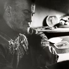 James Castle at desk in Cozy Cottage Trailer, Photograph by Jack McClarty, 1963, Tom Trusky Papers, Special Collections and Archives, Boise State University