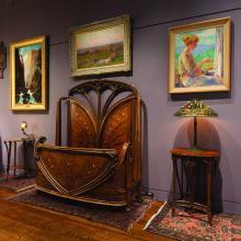 Kirkland Museum Art Nouveau Vignette featuring Aux Orchidées Bed (c. 1899–1900) designed by Louis Majorelle; Dragonfly Lamp (designed 1899) by Clara Wolcott Driscoll on Majorelle Table (c. 1900); Marquetry Table (left; c. 1900) designed by Émile Gallé