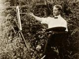 Artist Arthur Heming paints while standing in a forested area near the border of the Florence Griswold property. Courtesy of the Florence Griswold Museum